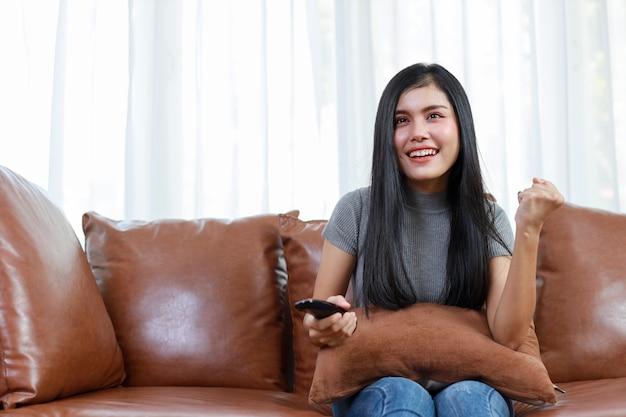 Tv en geluk concept. mooie aziatische vrouw in casual zittend op de bank in de woonkamer, televisie op afstand houdend en kijkend naar iets met een blij lachend gezicht. levensstijlconcept.