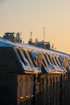 Tv- en kabelantennes op het dak van een appartementencomplex bedekt met sneeuw bij zonsondergang.