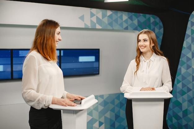 Tv game show met twee deelnemers staan op tribunes. opgewonden vrouwen in tv-studio, filmen tv-show.