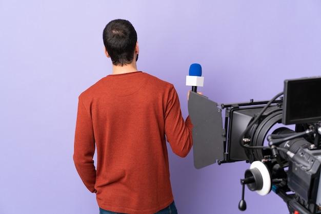 Tv-journalist of verslaggever met microfoon en videocamera, zicht naar achteren