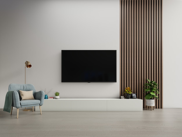Tv op de kast in moderne woonkamer met fauteuil op witte donkere muur.