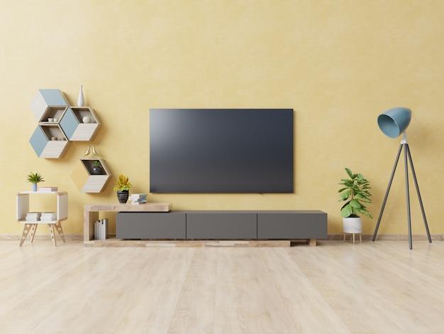 Tv op kast in moderne woonkamer met lamp, tafel, bloem en plant op gele muur.