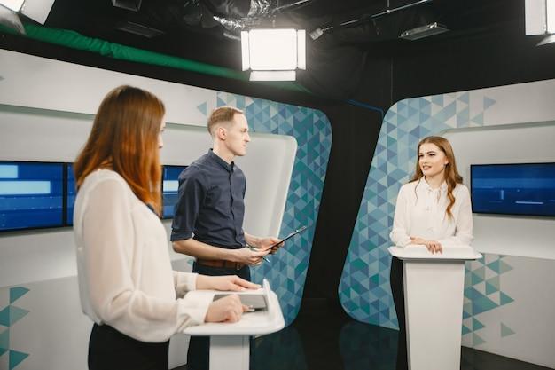 Tv-spelshow met twee deelnemers die vragen beantwoorden of puzzels oplossen en gastheer zijn. glimlachende vrouwen nemen deel aan televisiequiz.