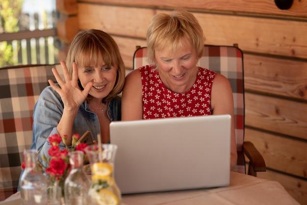 Twee 55-jarige vrouwen videobellen met een vriend die in zelfisolatie zit