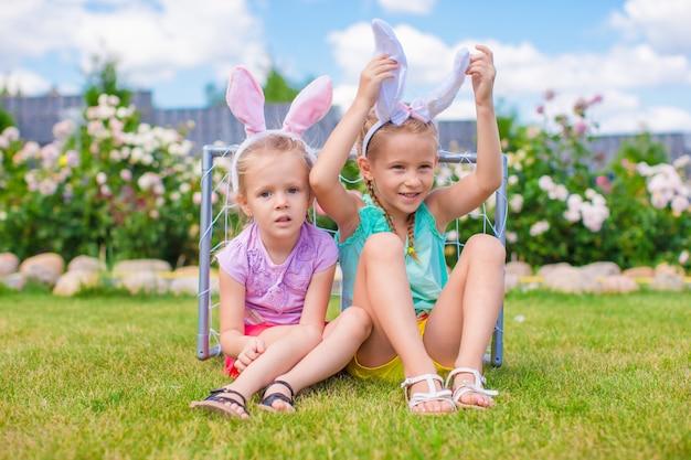 Twee aanbiddelijke kleine zusters die konijntjesoren op pasen-dag in openlucht dragen