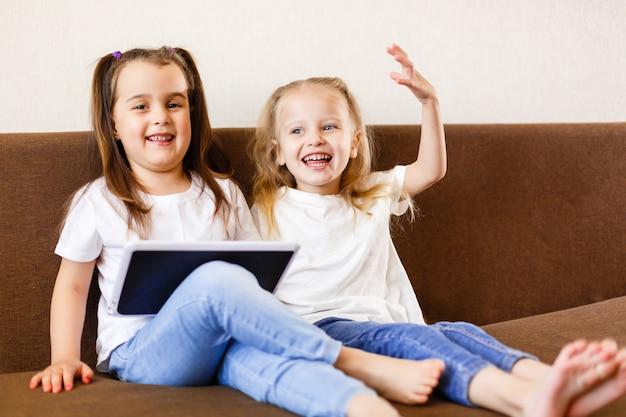 Twee aanbiddelijke kleine zusters die met een digitale tablet spelen die thuis zuster met de computer van tabletpc glimlachen