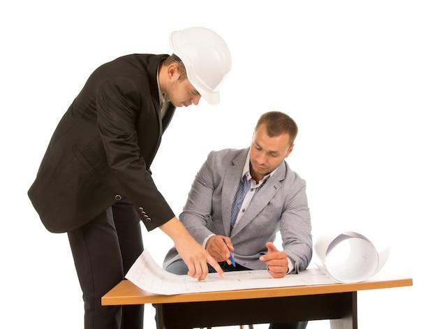 Twee aannemers die een blauwdruk bespreken