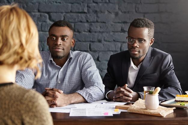 Twee aantrekkelijke afro-amerikaanse hr-specialisten die een sollicitatiegesprek voeren met een vrouwelijke kandidaat