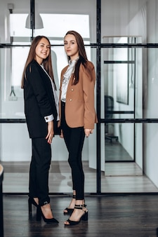 Twee aantrekkelijke bedrijfsmeisjes die in het werkbureau stellen