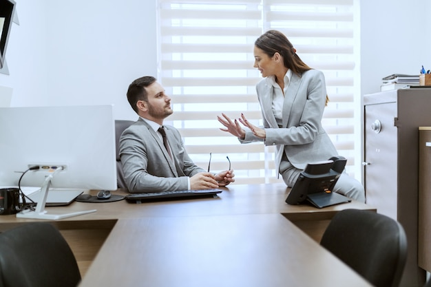 Twee aantrekkelijke blanke collega's gekleed in formele kleding zitten in kantoor en chatten.