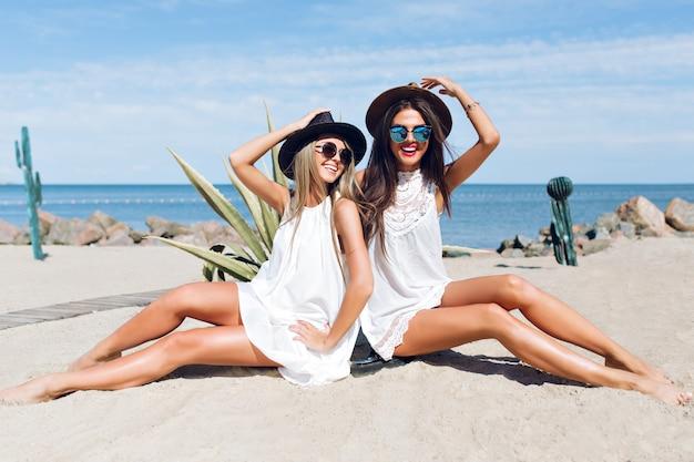Twee aantrekkelijke brunette en blonde meisjes met lang haar zitten op het strand in de buurt van zee. ze poseren en glimlachen naar de camera.