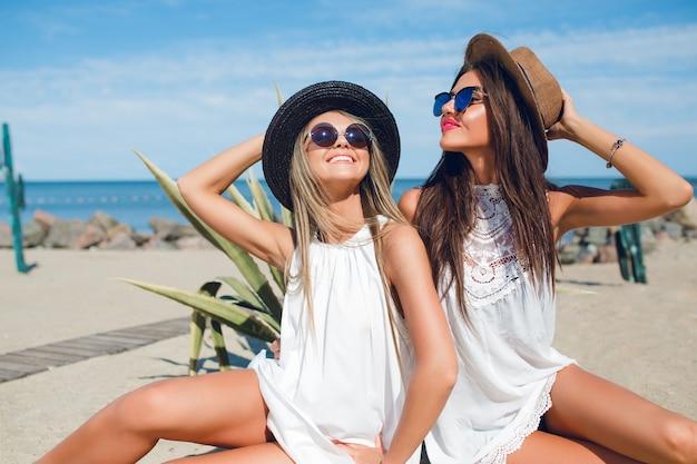 Twee aantrekkelijke brunette en blonde meisjes met lang haar zitten op het strand in de buurt van zee. ze poseren en glimlachen.