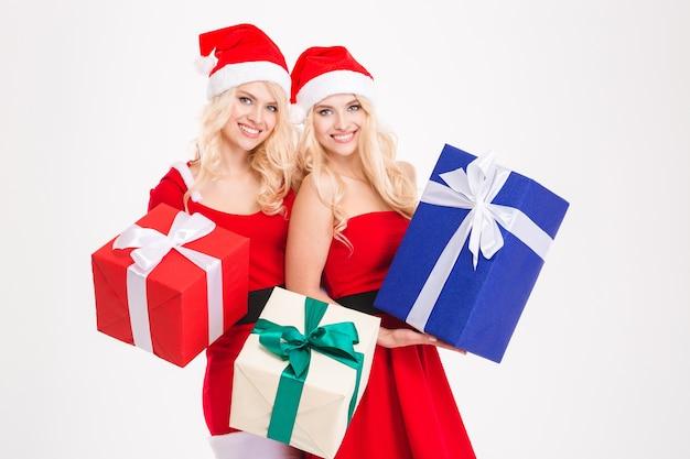 Twee aantrekkelijke gelukkige zussen tweeling in santa claus kostuums en hoeden met cadeautjes op witte achtergrond