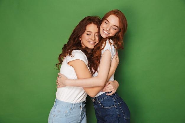 Twee aantrekkelijke gember meisjes 20s in vrijetijdskleding glimlachen en knuffelen elkaar met gesloten ogen, geïsoleerd op groene achtergrond