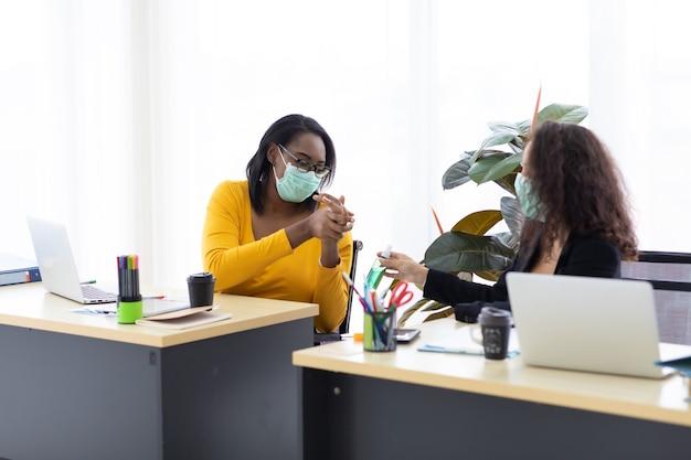 Twee aantrekkelijke jonge afro-amerikaanse en spaanse zakenvrouwen die een beschermend gezichtsmasker dragen, voorkomen dat het covid-19-virus zwarte koffie drinkt