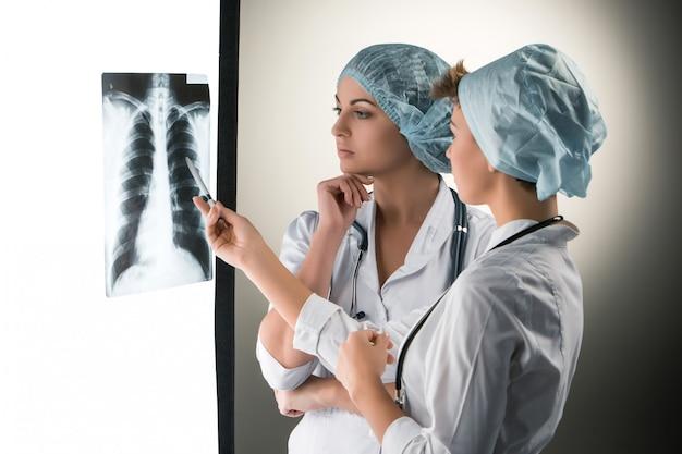 Twee aantrekkelijke jonge artsen die x-ray resultaten bekijken