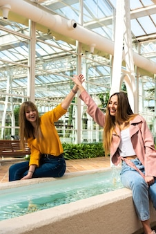 Twee aantrekkelijke jonge blanke meisjes met blond haar schudden elkaar de hand met hun armen in de lucht glimlachend bij een fontein in een helder verlichte kamer met de witte structuur