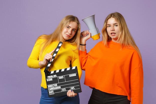 Twee aantrekkelijke jonge blonde tweelingzusters meisjes houden klassieke zwarte film maken filmklapper schreeuwen op megafoon geïsoleerd op violet blauwe muur. mensen familie levensstijl concept.