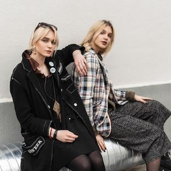 Twee aantrekkelijke jonge blonde vriendinnen in oversized stijlvolle kleding in retrostijl zitten op een zilveren metalen pijp in de buurt van de muur op straat