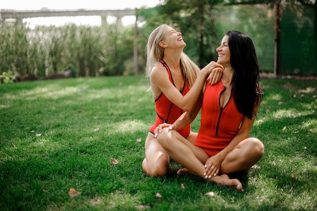 Twee aantrekkelijke jonge meisjes die op het groene gras in zwemkleding zitten