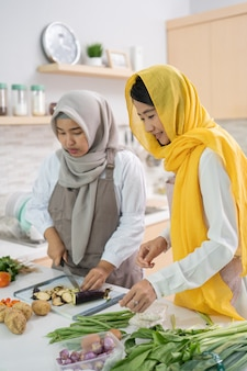Twee aantrekkelijke jonge moslimvrouw die iftardiner samen voorbereiden.