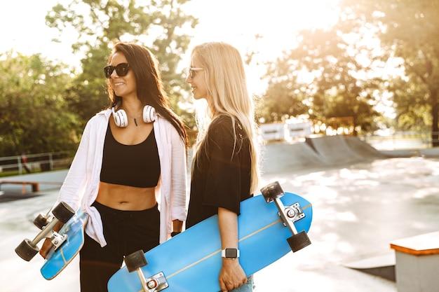 Twee aantrekkelijke jonge tienermeisjes die longboards vasthouden terwijl ze in het skatepark staan