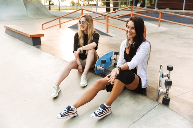 Twee aantrekkelijke jonge tienermeisjes zitten met longboards in het skatepark, praten