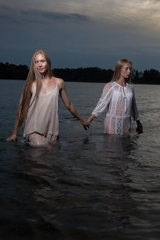 Twee aantrekkelijke jonge tweelingzusjes met lang blond haar poseren in lichte jurken in het water van het meer 's nachts