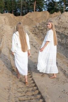 Twee aantrekkelijke jonge tweelingzusjes poseren bij zandgroeve in elegante witte kleren