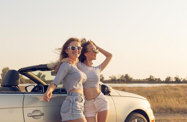 Twee aantrekkelijke jonge vrouwen in de buurt van een converteerbare auto