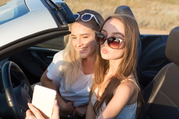 Twee aantrekkelijke jonge vrouwen in een cabriolet auto