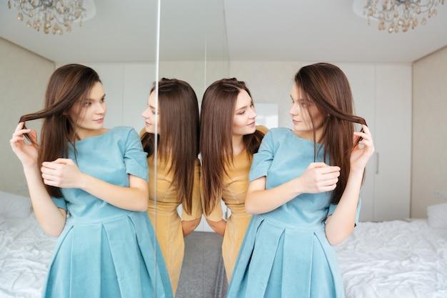 Twee aantrekkelijke jonge zussen tweeling staan in de kamer en kijken naar de spiegel