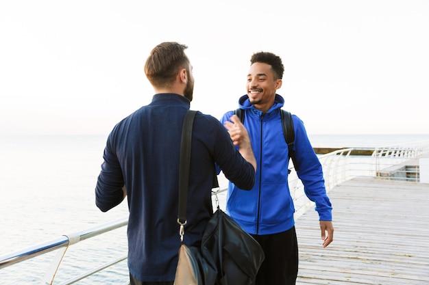 Twee aantrekkelijke lachende jonge gezonde sporters buiten op het strand, handen schudden?