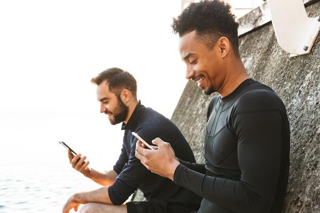 Twee aantrekkelijke lachende jonge gezonde sporters buiten op het strand, met behulp van mobiele telefoons