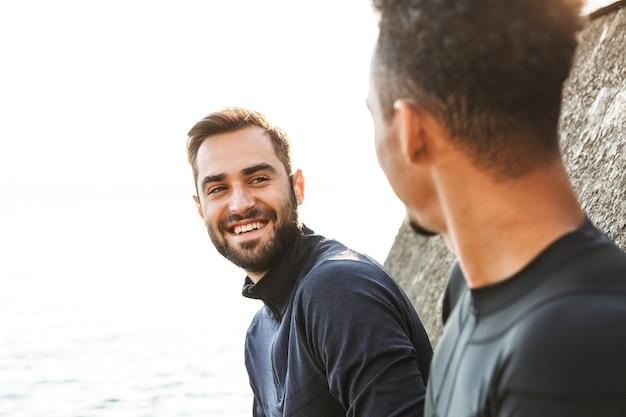 Twee aantrekkelijke lachende jonge gezonde sporters buiten op het strand, praten