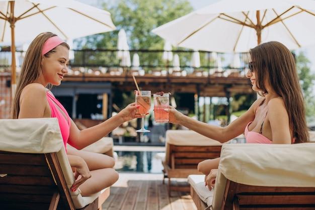 Twee aantrekkelijke meisjes die cocktails drinken bij het zwembad
