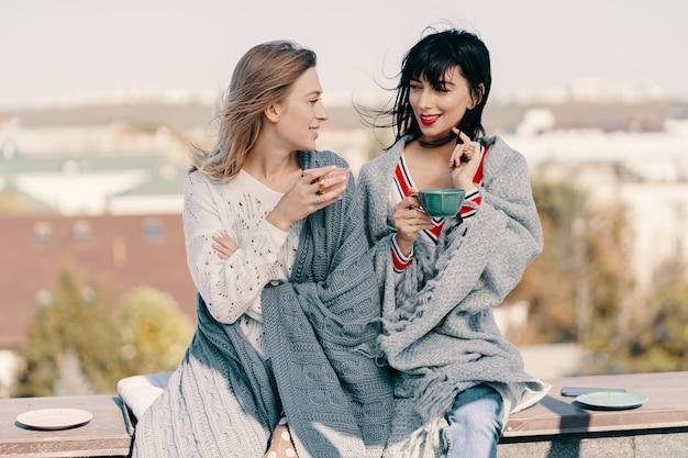 Twee aantrekkelijke meisjes genieten van een theekransje op het dak met uitzicht op de stad