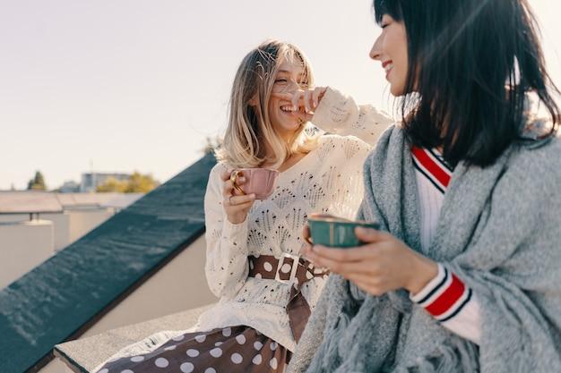 Twee aantrekkelijke meisjes genieten van een theekransje