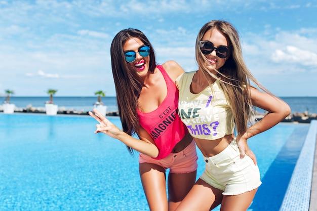 Twee aantrekkelijke meisjes met lang haar poseren in de buurt van zwembad op de zon. ze glimlachen naar de camera.