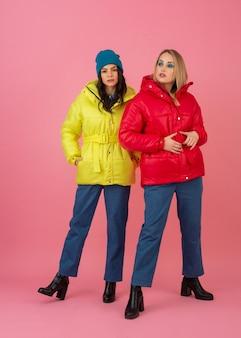 Twee aantrekkelijke meisjes poseren op roze achtergrond in kleurrijke winter donsjack van heldere rode en gele kleur