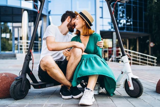Twee aantrekkelijke mensen chillen in de buurt van het glazen gebouw met hun electro-scooters. man en vrouw genieten van vakantie