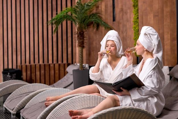 Twee aantrekkelijke ontspannen vrouwen kijken naar menu in spa salon procedures kiezen