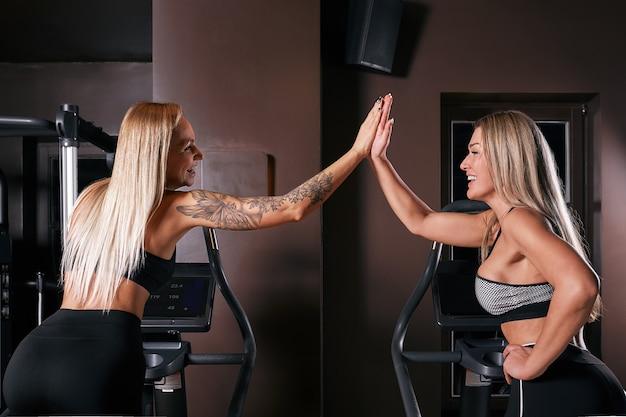 Twee aantrekkelijke sportieve vrouwen die hometrainers berijden tijdens het fietsen opleiding in gymnastiek