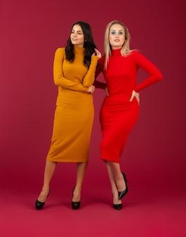 Twee aantrekkelijke stijlvolle vrouwen in gele en rode herfst winter mode gebreide jurk poseren geïsoleerd op rode muur