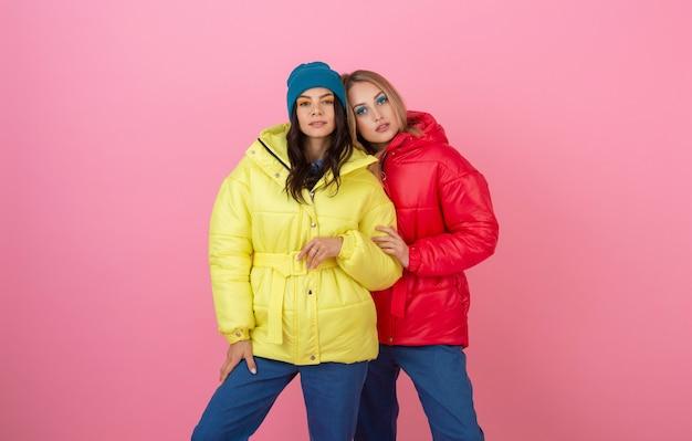 Twee aantrekkelijke stijlvolle vrouwen poseren op roze achtergrond in kleurrijke winter donsjack van rode en gele kleur, warme kleding modetrend