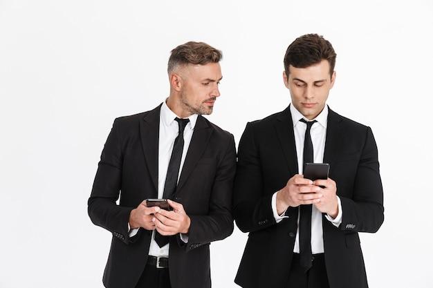 Twee aantrekkelijke verdachte zakenlieden die pakken dragen die geïsoleerd staan en naar elkaar mobiele telefoons kijken