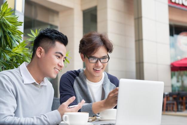 Twee aantrekkelijke volwassen studenten praten en werken buitenshuis op laptop