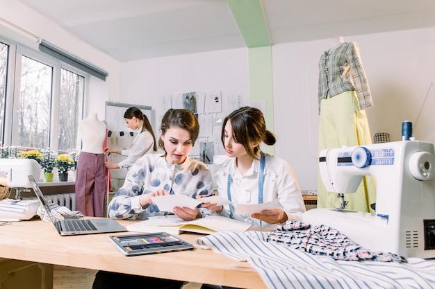 Twee aantrekkelijke vrouwelijke naaistersontwerpers die trendy schetsen en materialen kiezen voor een nieuwe kledingcollectie, terwijl een jonge meisjesontwerper werkt aan een nieuw model, een broek op paspop in de studio aanpassen