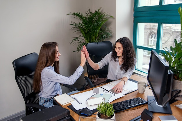 Twee aantrekkelijke vrouwelijke ontwerpers in blauwe shirts werken samen met een nieuw project op pc in het moderne kantoor. de meisjes klappen elkaar in de palm.