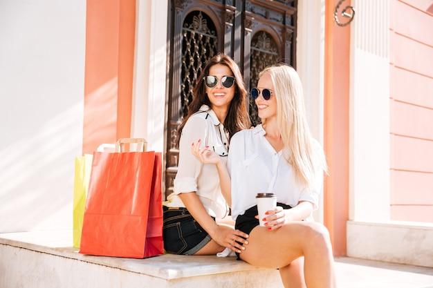Twee aantrekkelijke vrouwen houden papieren kopjes koffie en chatten na het winkelen